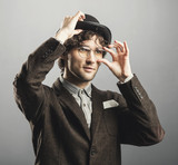 Man in retro clothes raising his hat and glasses.
