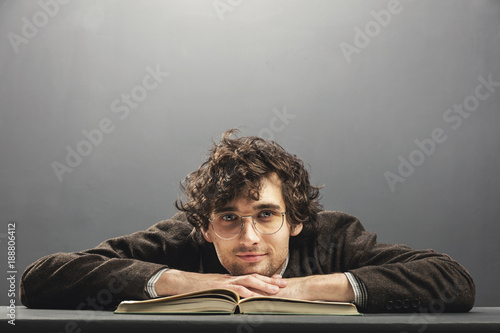 Young man in old glasses resting his head on a book.