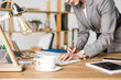 partial view of businesswoman making notes in notebook at workplace with cup of coffee
