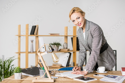 portrait of smiling businesswoman looking at camera while making notes in notebook at workplace