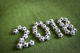 Sporty New Year 2018 message formed from soccer balls on green football pitch background