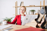 portrait of businesswoman with newspaper at workplace - 188809656