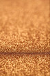 Portrait image at 45 degree angle of gold glitter background iwith blur