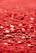 Image of red heart shape glitter with blur taken at a 45 degree angle.