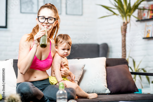 Sports mom drinking fresh green smoothie after the training sitting with her baby boy on the couch at home