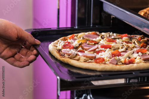 Fotobehang Pizzeria hand moves the tray of pizza with mushrooms, ham and mozzarella cooked baking in the oven.
