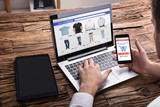 Businessperson Using Smartphone While Shopping Online On Laptop - 188825241
