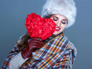 happy young woman isolated on cold blue background holding red heart