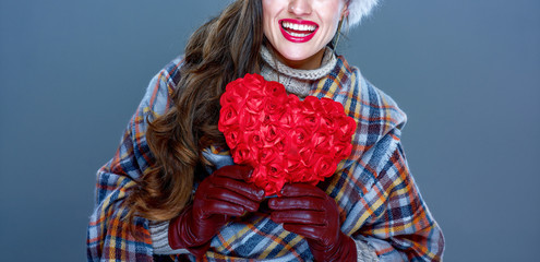 smiling elegant woman isolated on cold blue with red heart
