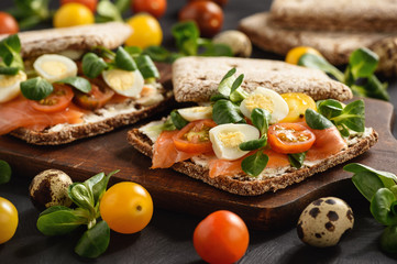 Smoked salmon sandwiches with tomatoes and eggs.