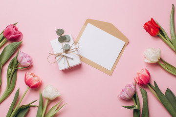 Gift and card on a pink background with tulips. Flat lay and top view.