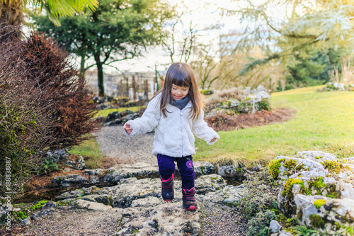 Happy child in a garden - looking for spring elements