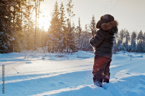 Boy walking on winter snowy road with sunny forest on background. Urals landscape