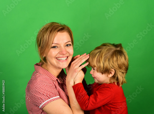 Woman and little boy with smiling faces on green background