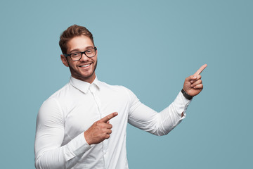Cheerful muscular man pointing on side