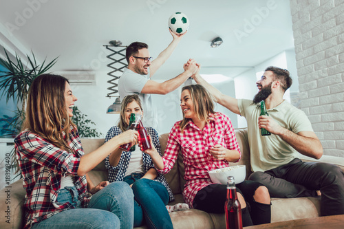 Happy friends or football fans watching soccer on tv and celebrating victory at home.Friendship, sports and entertainment concept.