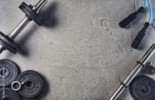 Fototapeta Fitness or bodybuilding concept background. Product photograph of old iron dumbbells on grey, conrete floor in the gym. Photograph taken from above, top view with lots of copy space