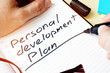 Man writing Personal development plan in a note.