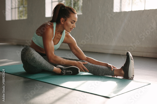 Fit woman doing stretching workout at gym