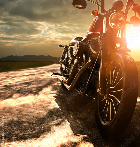 Fotobehang Fiets old retro motorcycle traveling on country road against beautiful light of sunset sky