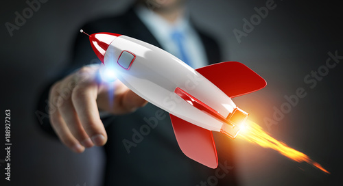 Fototapeta Businessman holding and touching a rocket 3D rendering