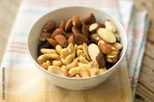 Little bowl of. mixed nuts (almonds, cashews and Brazil nuts) on the wooden table