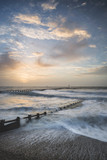 Beautiful dramatic stormy landscape image of waves crashing onto beach at sunrise - 188950427