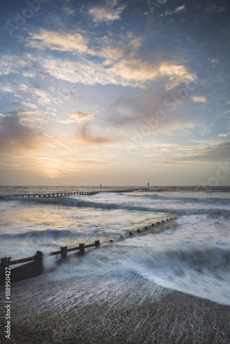 Beautiful dramatic stormy landscape image of waves crashing onto beach at sunrise