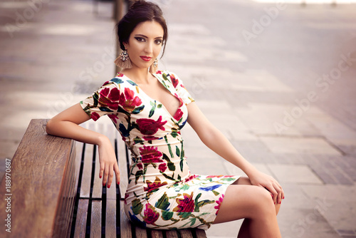 beauty brunette girl with a flowers dress in street sitting on a bench