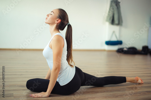 Obraz na płótnie woman practicing yoga pose at yoga healthy sport gym, girl stretching her legs
