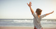 Leinwandbild Motiv happy woman enjoying freedom with open hands on sea