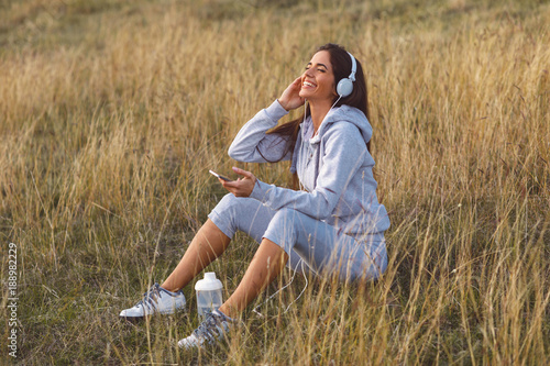 Young woman resting and listening to music after jogging