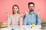 Isolated shot of two female and male coworkers, meditate and keeps eyes shut, try to relax after exam preparation, cramm material from many books, sit at working desk against pink background - 189005287