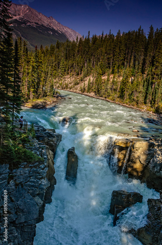 a view from above on the rough streams of a mountain river among green forests and rocky mountains - 189008849
