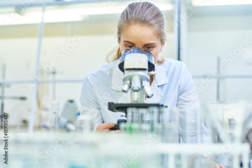 canvas print picture Portrait of young female scientist looking in microscope while working on medical research in science laboratory, copy space