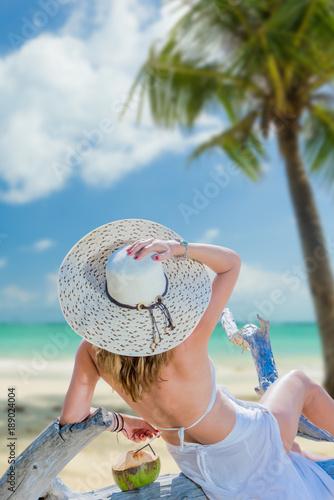 Woman in bikini with sunhat at the beach
