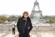 Mulatto male model smiling near Eiffel Tower.