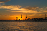 Silhouettes of industrial machines against sunset sky on the background
