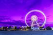 Leinwandbild Motiv Spinning ferris wheel at sunrise blue hour in Rimini, Italy. Long exposure abstract image