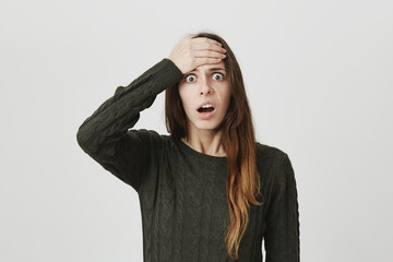 Isolated portrait of shocked european female with straight hair, dressed casually, feeling astonished to see something, keeping her hand on forehead, standing with popped eyes and opened mouth.