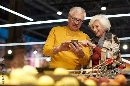 portrait of cheerful senior couple grocery shopping in supermarket