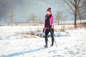Frau beim Nordic Walking im Winter für mehr Fitness