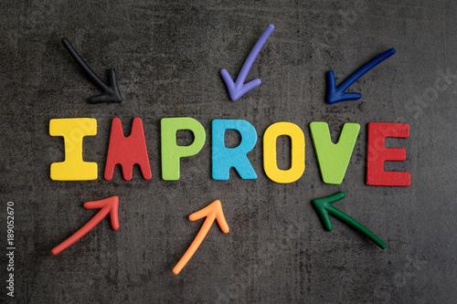 concepto-de-mejora-personal-mediante-flechas-multiples-que-apuntan-a-alfabeto-colorido-mejorar-en-el-centro-sobre-fondo-de-pared-de-cemento-negro-oscuro