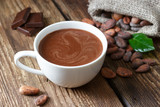 Hot chocolate in the cup on the wooden table. - 189054091