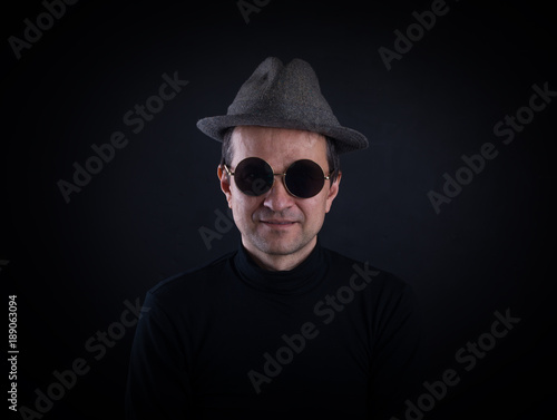 studio portrait of a man in a hat and sunglasses on a black background