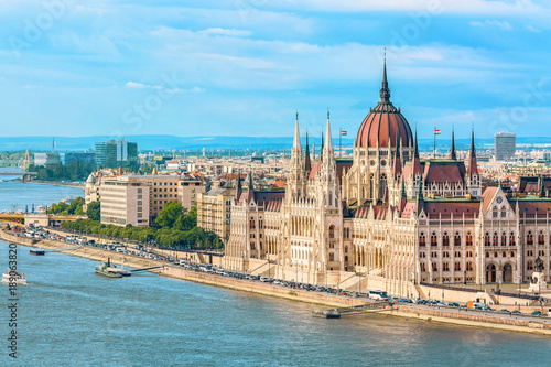 Travel and european tourism concept. Parliament and riverside in Budapest Hungary with sightseeing ships during summer day with blue sky and clouds