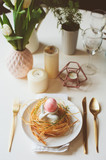 easter festive table details. Dining place decorated in pink and gold tones, with nest, bunny and eggs. - 189064054