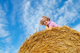 The cheerful girl of eight years in the field on a straw roll