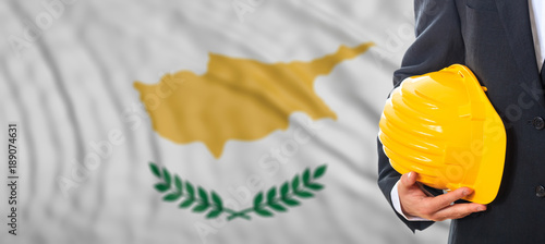 Foto op Canvas Cyprus Engineer holding a yellow hard hat on Cyprus waving flag background. 3d illustration