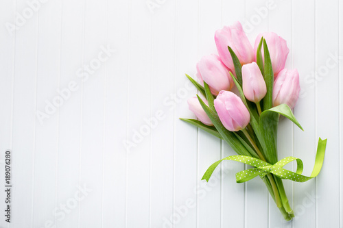 Fresh red tulip flowers bouquet on shelf in front of wooden wall.